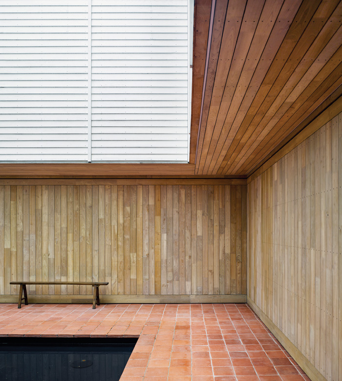 An inner open-air courtyard with a shallow square pool provides a space to sit and think