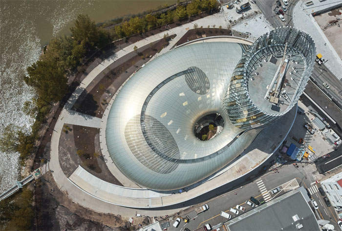 An Aerial view shows the proximity of the river. The building's shape has been variously interpreted by observers and fellow architects. Image Credit: Julien Lanoo