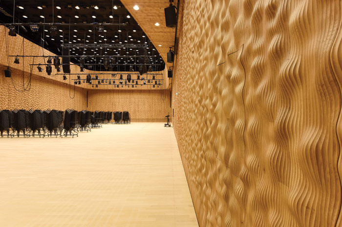 The Recital Hall is a shoebox shape lined with wooden contoured walls. Image Credit: Michael Zapf