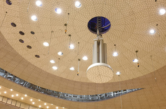 Equipment is lowered from the Grand Concert Hall's sound reflector that hangs from a vortex ceiling. Image Credit: Michael Zapf
