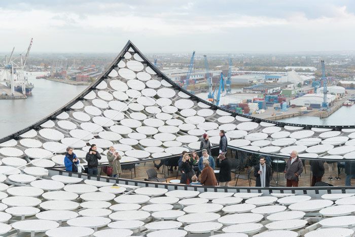 A terrace cuts into the wave roof. Image Credit: Iwan Baan