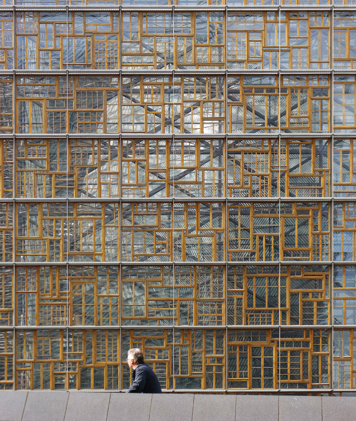 Salvaged wooden window frames are mounted across two facades of the Europa building. Image Credit: Thierry Henrard