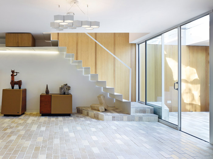 A minimal, bespoke staircase connects the studio space and home, while wood joinery and brick tiles nod to mid-century design