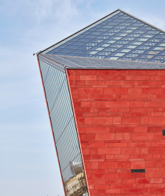 The tower has a roof of two clear triangles and facades that are trapezoids, three of them clad with red concrete