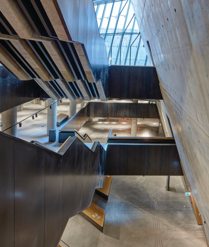 Two massive staircases descend in the museum's vast underground space