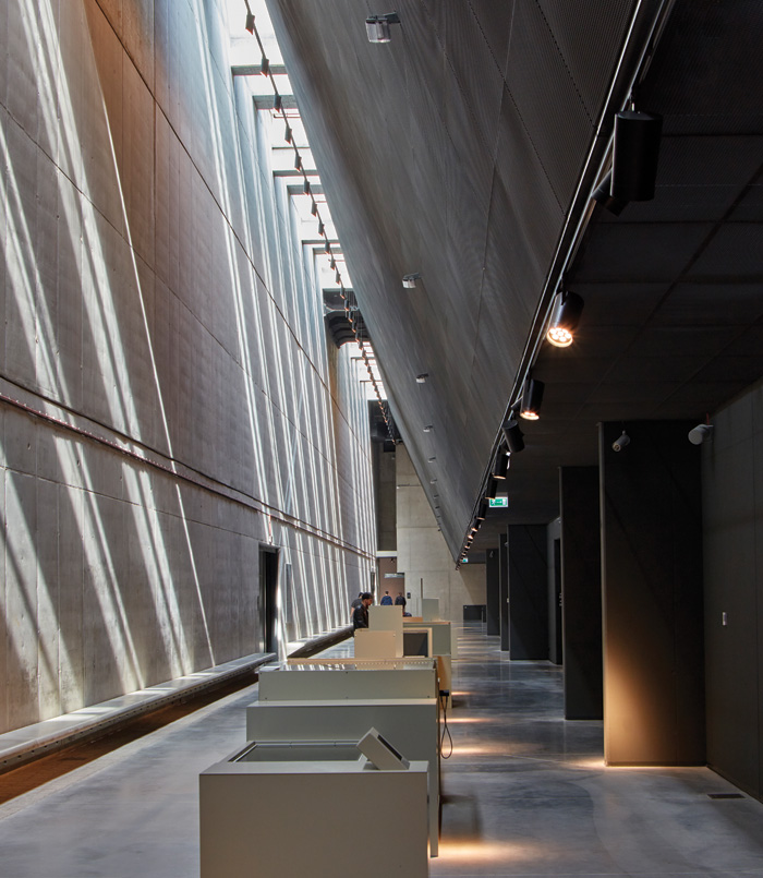 Morning light casts beams across the sheer concrete wall that defines the axis of the permanent exhibition