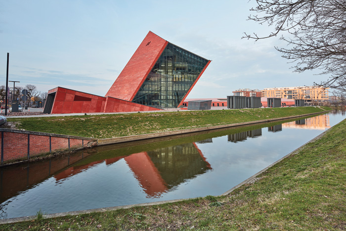 The museum is located beside a canal. Underground car parking is accessed through the wedge-shaped volume