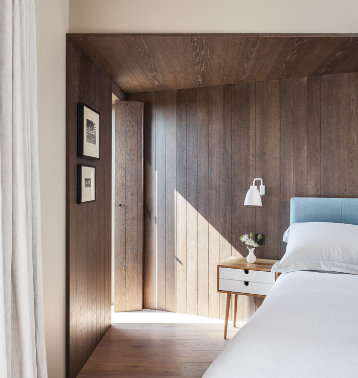 Wooden joinery brings a sense of warmth to the bedroom, while a window near the head of the bed provides views out to the landscape