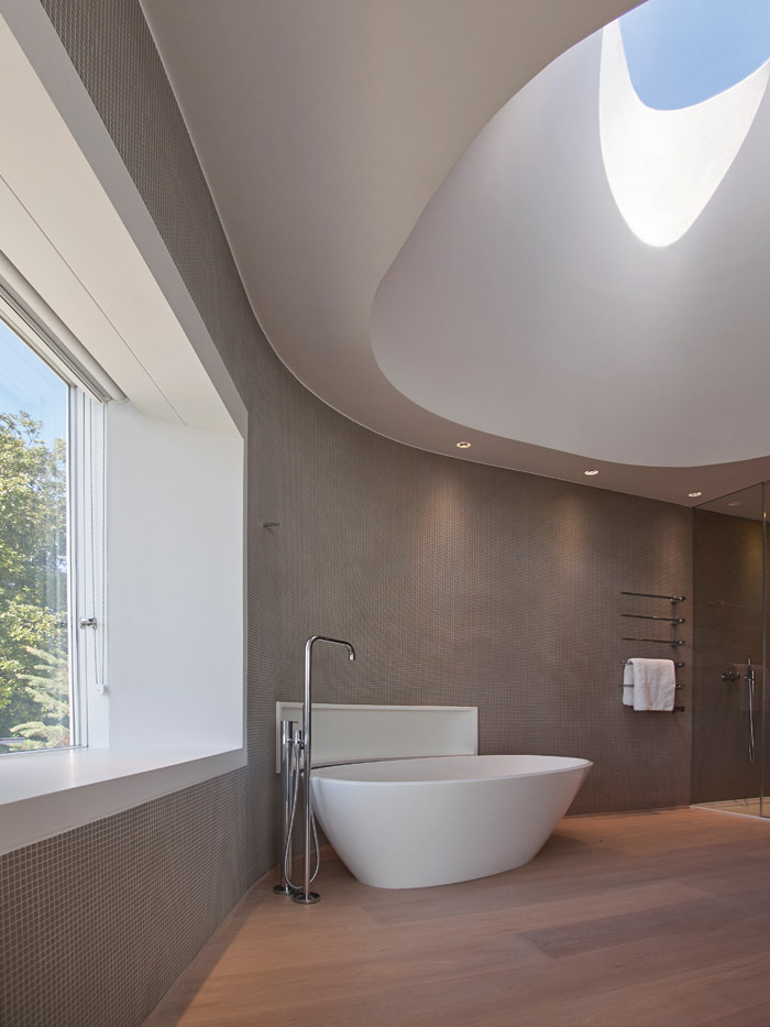 The bathroom features a curved bath, which echoes the sculptural, twisting skylight above it