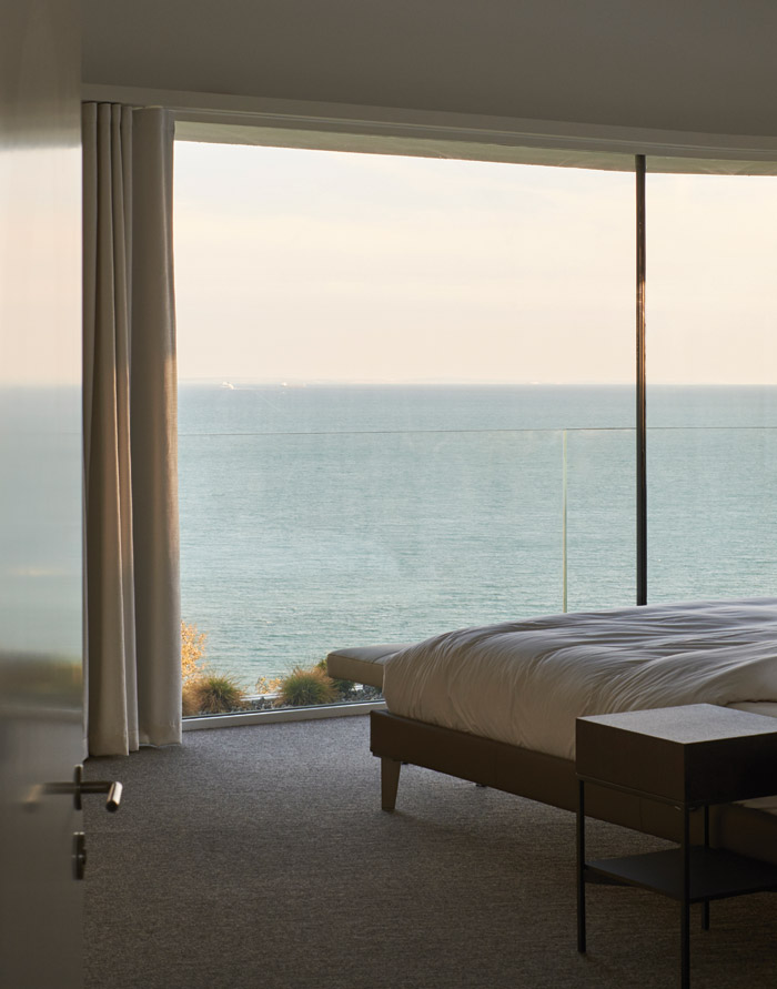 The vast swathes of glass and views out to sea give the bedroom the appearance of being on a boat