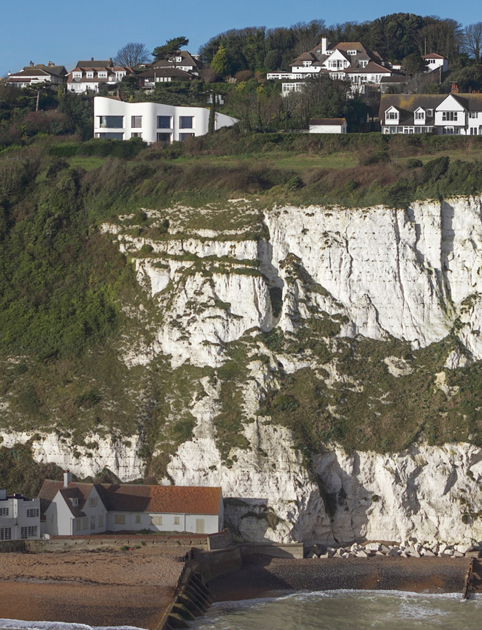 The white house with its angled roof is just visible above the ragged clifftops. It perches just 50 metres from the edge. Photo Credit: Robby Whitfield