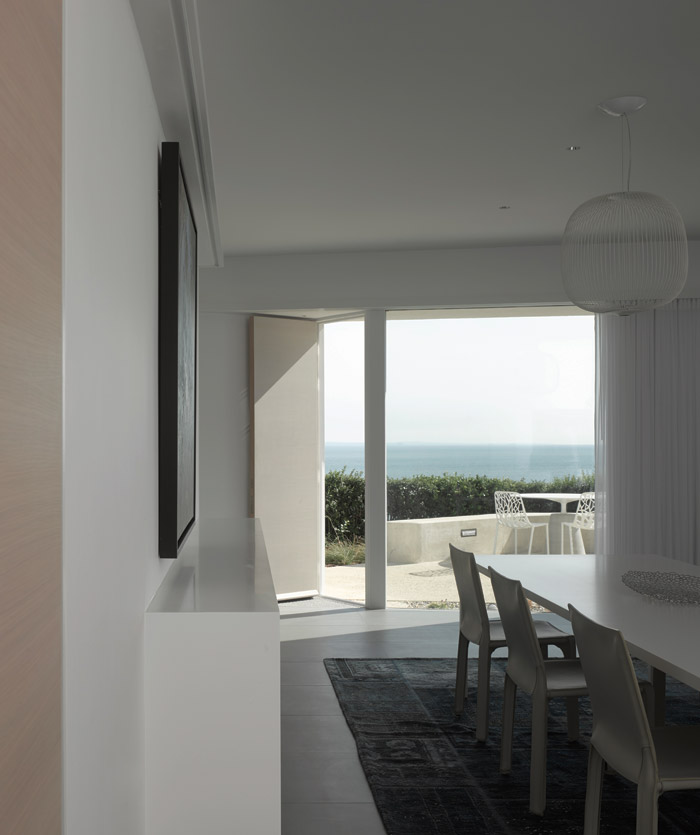 The dining space sits adjacent to the living room and also looks out to sea. Photo Credit: Nick Guttridge