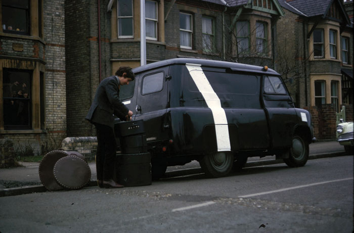 Drummer Nick Mason loads up the Bedford van with its unusual paint job, in which the band criss-crossed the country building up a following. Image Credit: Pink Floyd Archive