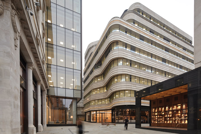 The new St James's Market development in London's West End comprises two buildings that face each other to create a small public space in the middle. They are designed to complement each other; while one responds to the existing historic buildings, the other is all curves