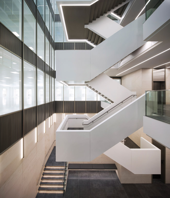The monolithic form of 1SJM's elegant, Corian staircase is highlighted by integrated lighting and bronze accents