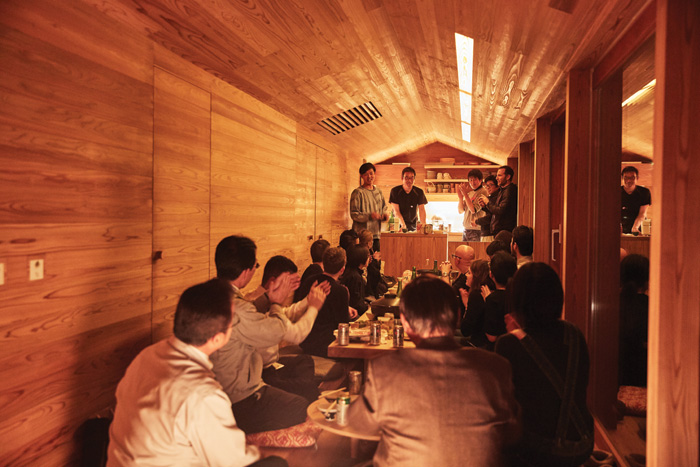 The inaugural celebration meal at the Yoshino Cedar House, with Joe Gebbia standing up far right. Image Credit: Ryan Kim