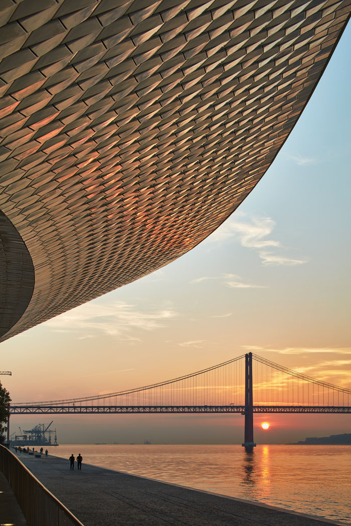 As the sun rises behind the 25 de April Bridge (opened 1966), its light starts to play on the ceramic tiling