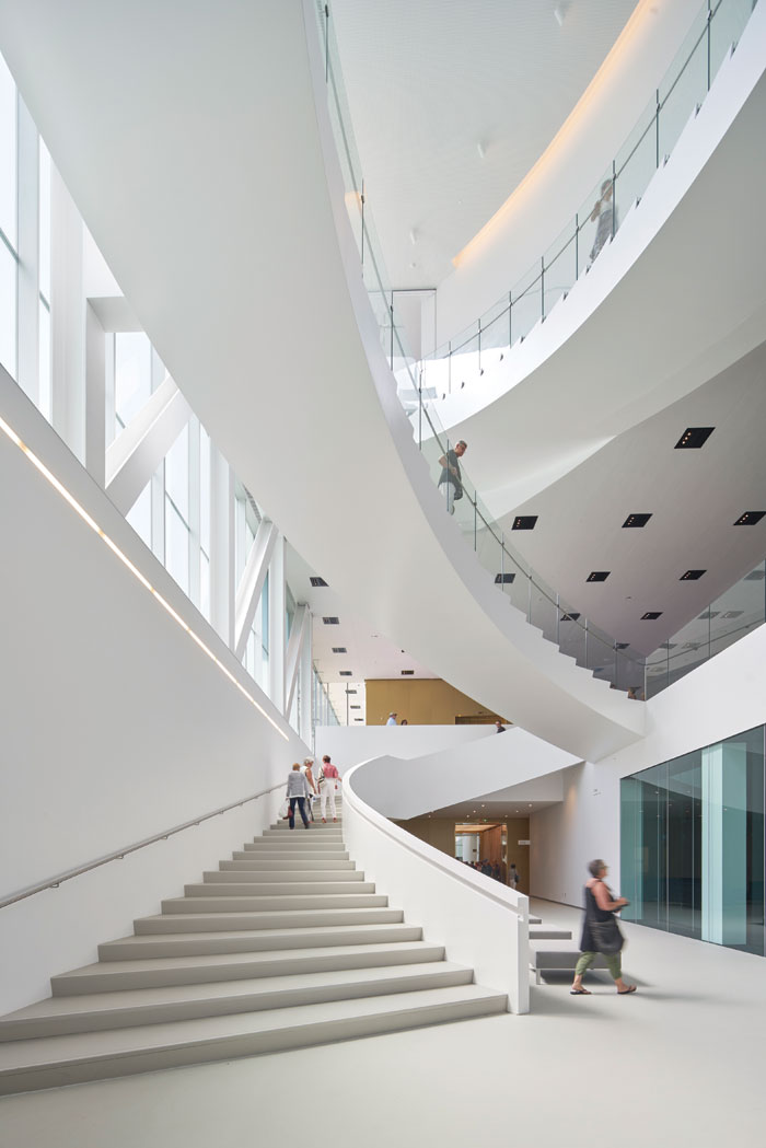 The sweeping staircases are an organic statement within the rigid, rectilinear, box volumes. Image: Bruce Damonte