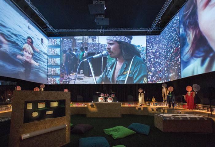 Footage from Woodstock plays in an immersive hang-out space in the show. Photography - Victoria and Albert Museum, London