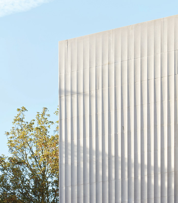 Light and shadow is cast on the hand-finished fluted limestone facade, which also include stone and bronze