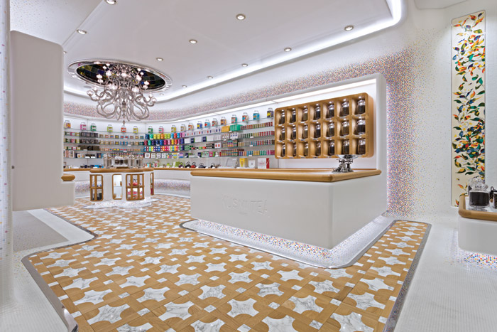 The flooring, mosaic-tile detail and the marquetry panels and packaging create a brightly coloured interior against a crisp white background