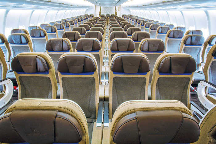 Seats in economy class cabin, a large element in the space, are in calm tones with splashes of blue