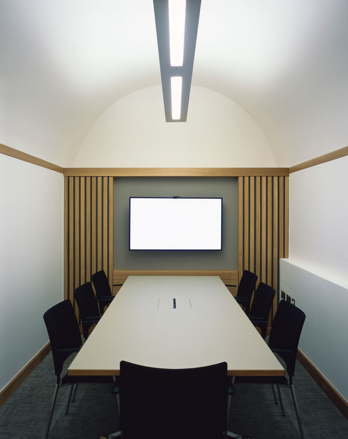The space's vaults with barrelled ceilings and bespoke cabinetry now house small meeting areas