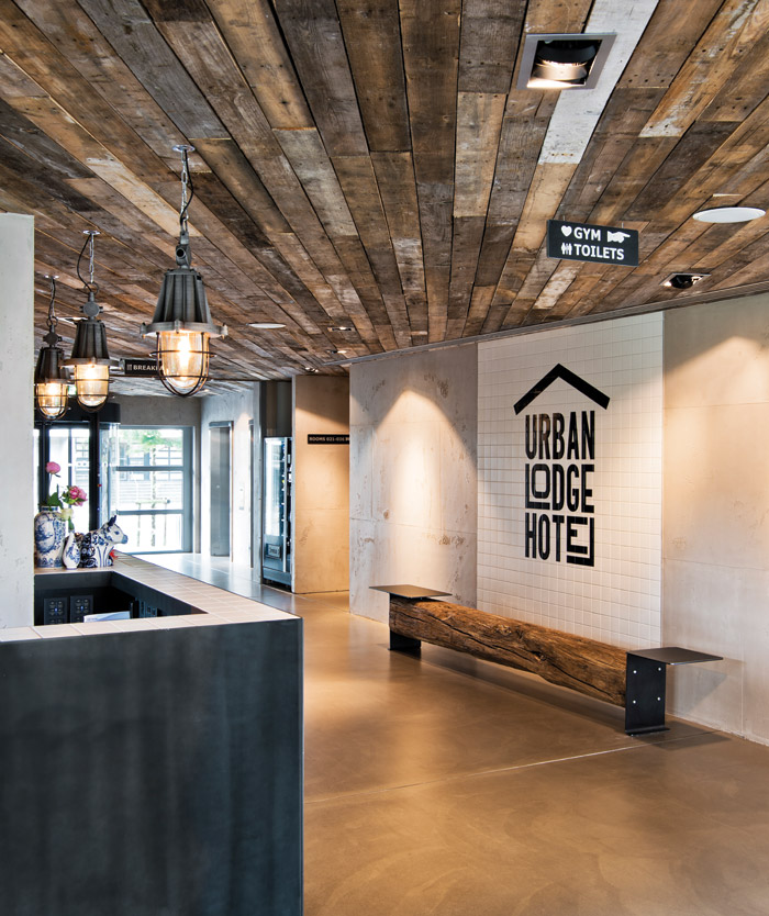Reclaimed timber planking creates a striking ceiling in the reception area, contrasted by a concrete floor