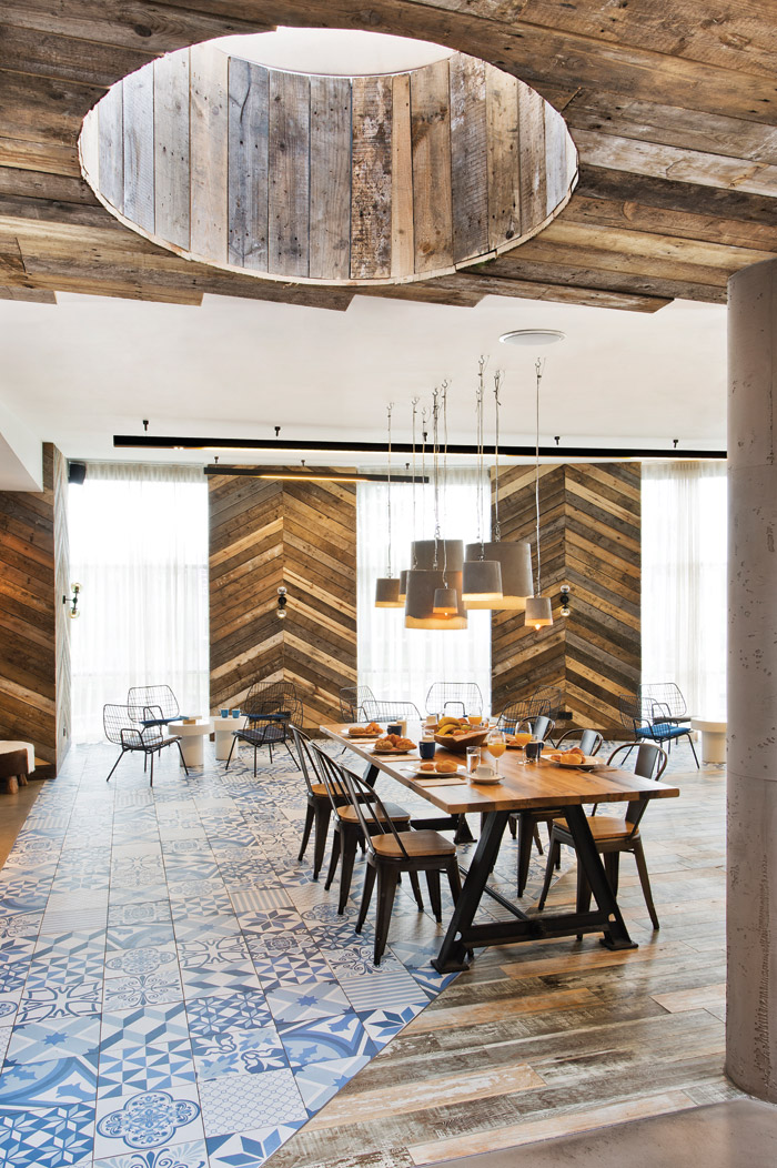 The reclaimed planking goes into chevrons on the wall, while the flooring melds into blues and whites for the Delft Pottery theme bar area