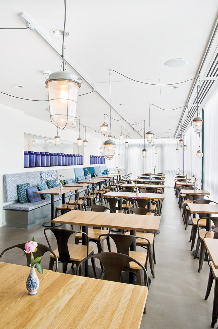 Splashes of blue appear amid locally reclaimed industrial lighting used in the dining space
