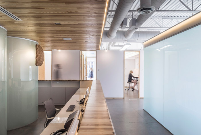 The six examination rooms, featuring frosted glass ceilings, form a long white wall punctuated by six high wooden doors. With an opalescent glass wall and lowered ceiling, the relaxation room for the clinic's professionals looks like a glowing cube