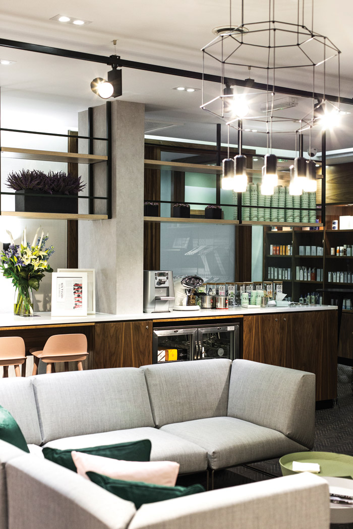 The lounge area features a central drinks and coffee bar, and furniture to help waiting patients either relax or work before their appointments