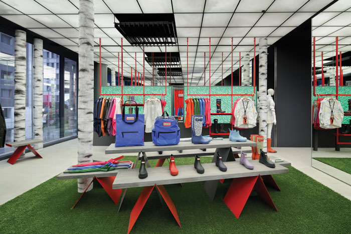 Garments and footwear are displayed on units sitting on a lawn of artificial turf below an illuminated 'sky' in a 53 sq m light box