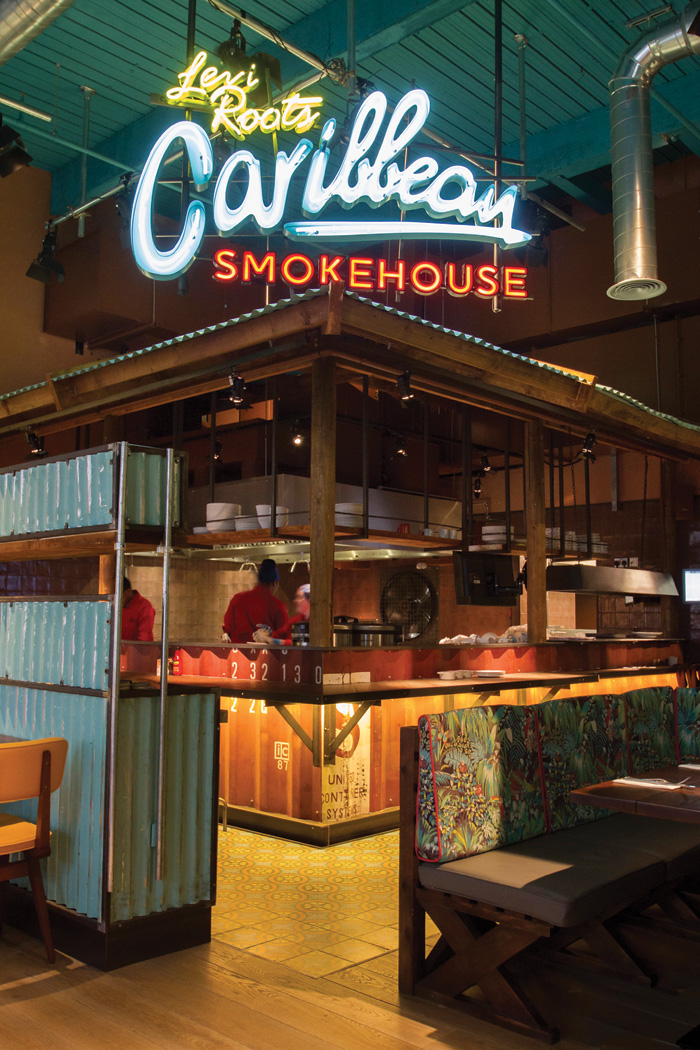 An illuminated restaurant logo sits over the corrugated roof and timber frame of the cooking pit shack