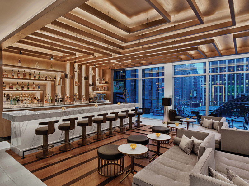 The sixth-floor bar has a elaborate ceiling of geometric-shaped walnut frame panelling that extends down behind the bar and is echoed in the flooring