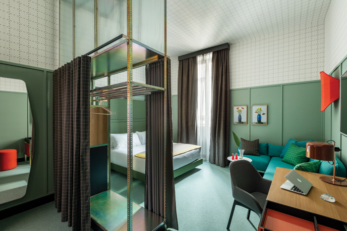 In this junior suite, wardrobes are minimalist to resemble industrial shelving, offset by fabric and wood