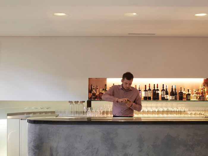 A white ceramic floor reflects daylight into the bar space, with its bar in polished concrete