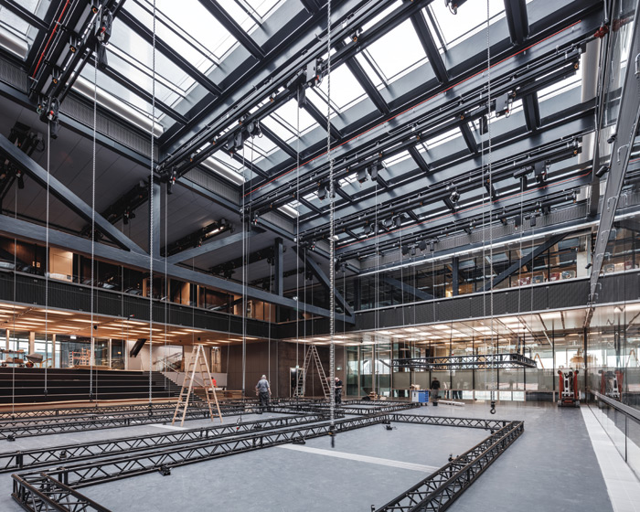 Technicians install rigs in the main DAC exhibition hall to prepare for a show, with the large steel structural trusses visible above. Credit: Rasmus Hjortshoj