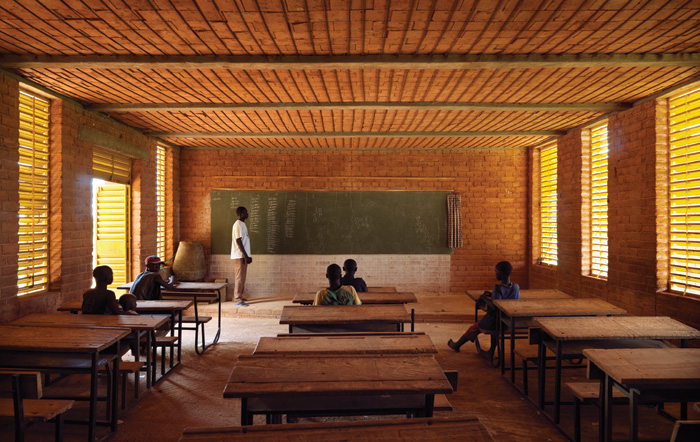 Kéré's first project was a primary school in his home village of Gando. The tin roof of the structure is pulled away from the inner perforated ceiling to aid ventilation Photo Credit: Enrico Cano