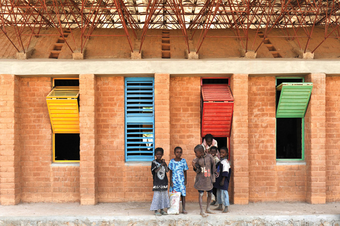 Kéré's first project was a primary school in his home village of Gando. The tin roof of the structure is pulled away from the inner perforated ceiling to aid ventilation. Photo Credit:  Erik Jan Ouwerkerk