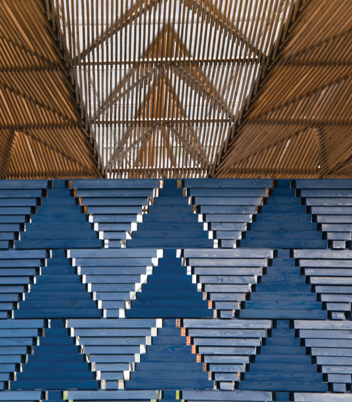 The blue wall system, made of triangular modules, appears like an African textile or screen