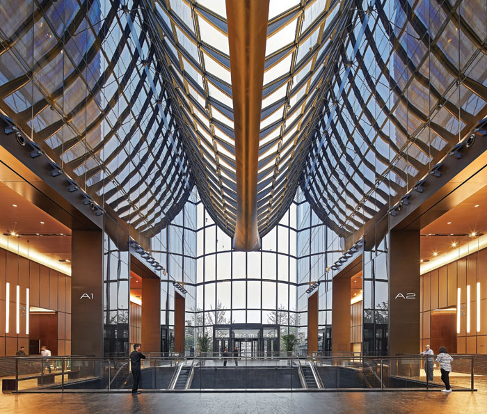A dipped glass atrium connects the two towers. Image Credit: Hufton+Crow