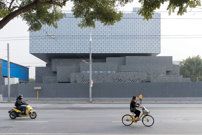 At the base of the building, interlocking cuboids of dark grey basalt align it with the surrounding area at street level. Photo Credit: Iwan Baan