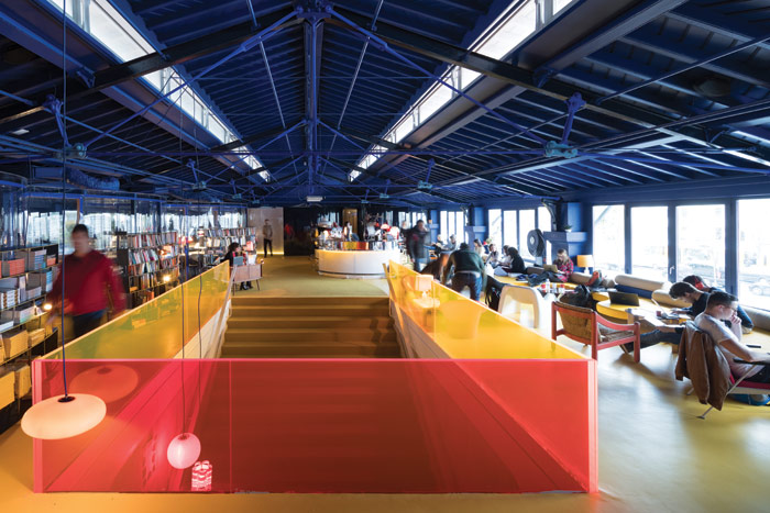 The original structure is painted bright Yves-Klein blue and a yellow staircase leads to the market below. A lending library with more than 2,000 books wraps around meeting rooms to the left