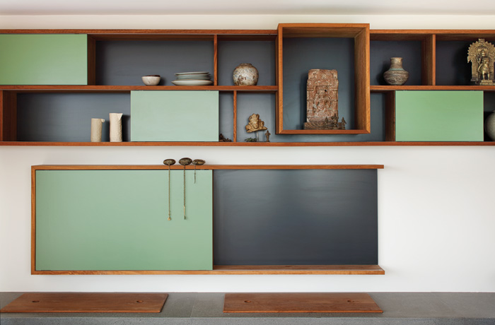 The dominant material in the house is timber, here in cupboards and shelving painted with touches of Fifties sage green.  Image Credit: Brotherton Lock