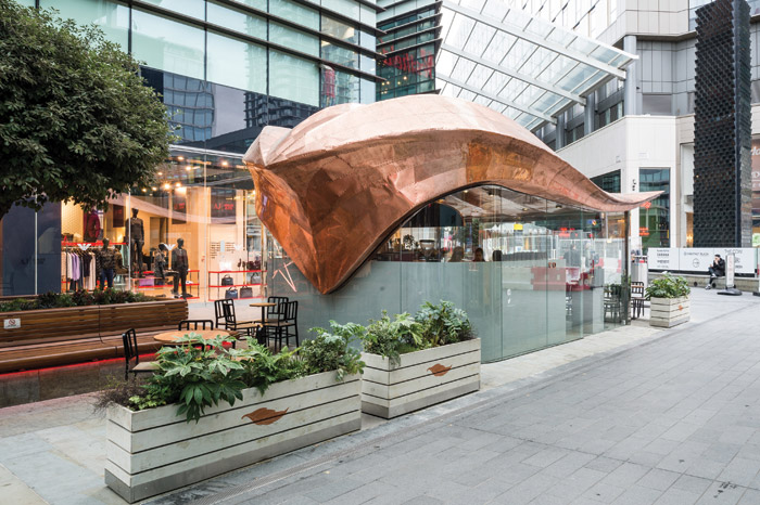 Colicci, Westfield: Appointed by coffee brand Colicci to design a cutting-edge kiosk at the entrance to the shopping centre, it had to act as a welcoming attraction while drawing visitors into the cafe. The design features a flowing sculptural roof clad in metal sheeting.