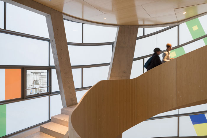 Internal views of the Maggie's Barts London, showing a curved staircase in bamboo