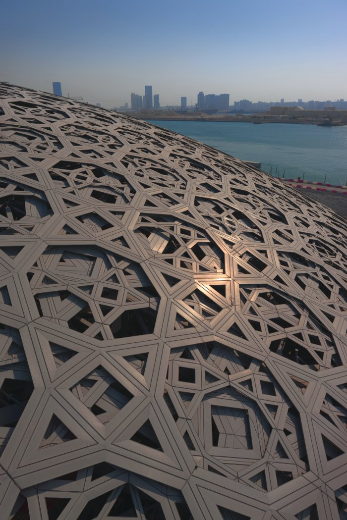 The roof is made up of eight layers of geometric metal star shapes, with four layers of stainless steel on top and aluminium underneath, held together by a steel frame. It weighs 7,500 tonnes.. Photo Credit: Abu Dhabi Tourism & Culture Authority, Jean Nouvel Architecte