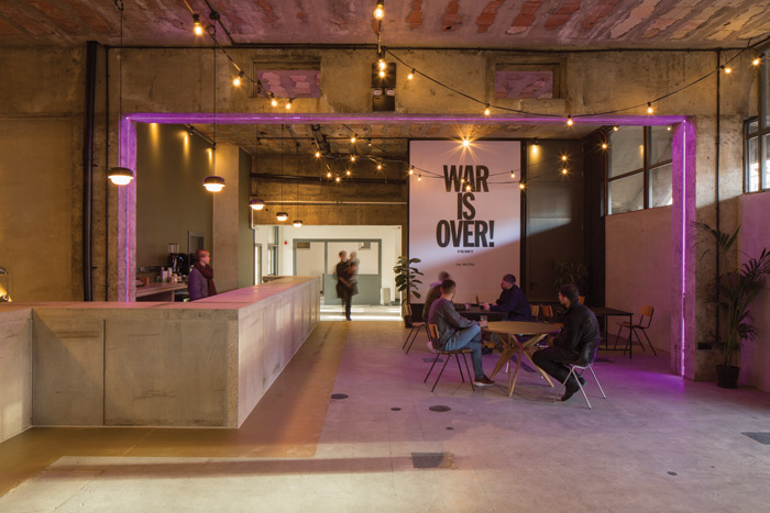 SODA's key intervention, the communal reception space, includes a freshly poured concrete bar to reflect the building's industrial materiality. Image Credit: Lewis Khan