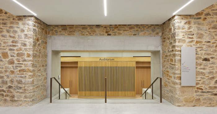 The original stone foundations are left exposed and complemented with concrete and wood paneling. Photo Credit: Hufton + Crow